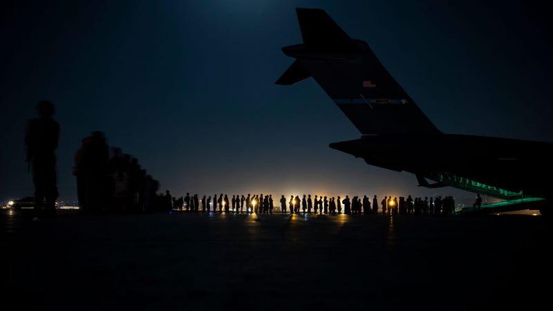 In this handout provided by the U.S. Air Force, an air crew prepares to load evacuees aboard a C-17 Globemaster III aircraft in support of the Afghanistan evacuation at Hamid Karzai International Airport on August 21, 2021 in Kabul, Afghanistan. (Photo by Taylor Crul/U.S. Air Force via Getty Images)