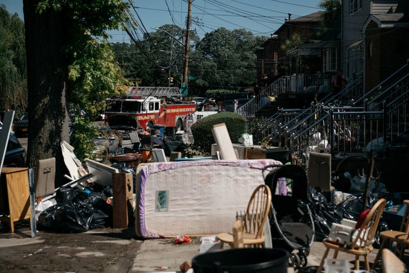 Residents sort through damaged and destroyed items after a night of heavy rain and wind caused many homes to flood on September 2, 2021 in the Flushing neighborhood of the Queens borough of New York City