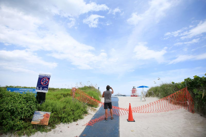 A man takes a photo of the beach next to fencing indicating that the beach is temporarily closed in South Pointe park on July 4th in the South Beach neighborhood of Miami Beach, Florida