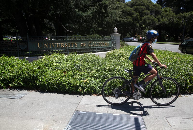 A cyclist rides by a sign in front of the U.C. Berkeley campus on July 22, 2020 in Berkeley, California