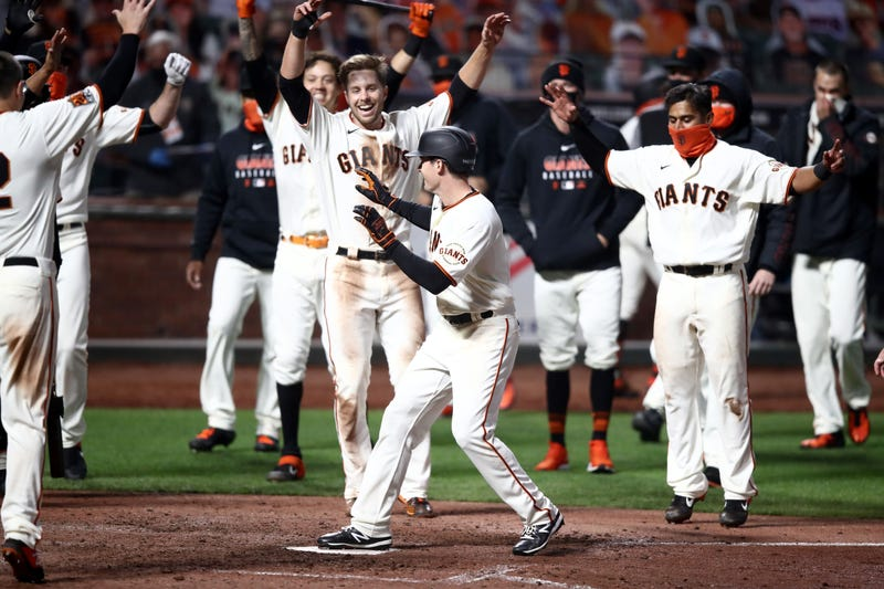 Teammates mobbing Mike Yastrzemski after his walk-off home run against the Padres