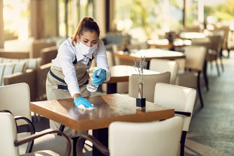 Waitress disinfecting table