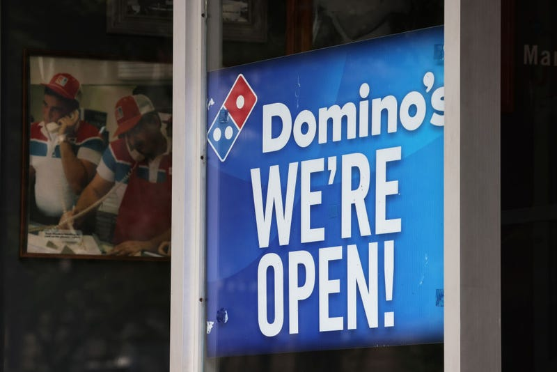 """A """"We're Open"""" sign is displayed on a window at a Domino's on August 19, 2020 in Brooklyn, New York. Domino's made an announcement on Tuesday that it is seeking to fill 20,000 positions at its corporate and franchise stores nationwide."""