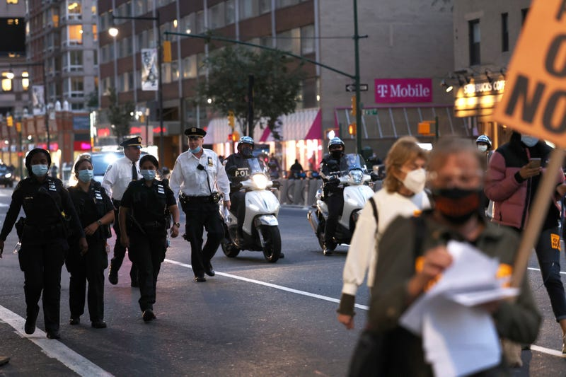"""NYPD officers walk behind demonstrators as they march against """"Death, Lies, and Fascism, and for Humanity!"""" on September 21, 2020 in New York City."""