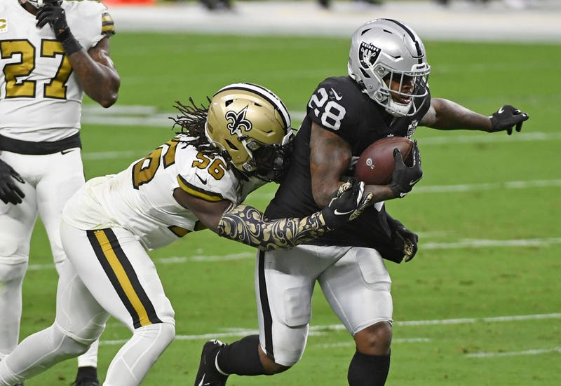 Josh Jacobs attempts to break out of a Saints defender's tackle.