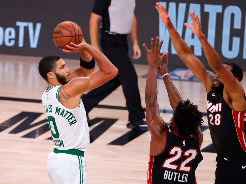Celtics forward Jayson Tatum attempts a shot against Heat defenders Jimmy Butler and Andre Iguodala