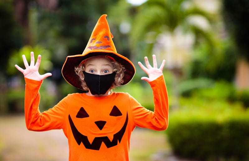 Child in Halloween costume and face mask