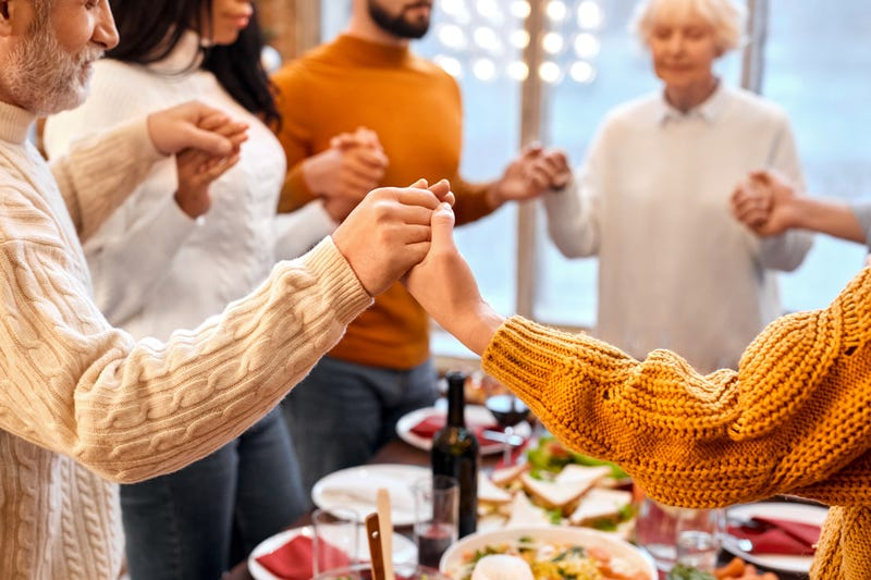 family holds hands during prayer before holiday dinner at home
