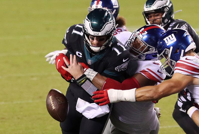 Carson Wentz gets wrapped up by a Giants defender.