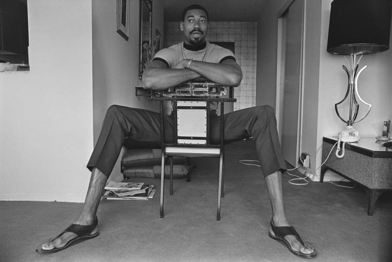 Wilt Chamberlain's height is on display even as he sits down in a chair.