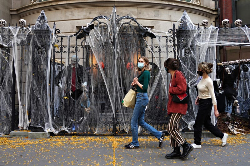People walk by Halloween decorations outside of an Upper East Side home on October 24, 2020 in New York City.
