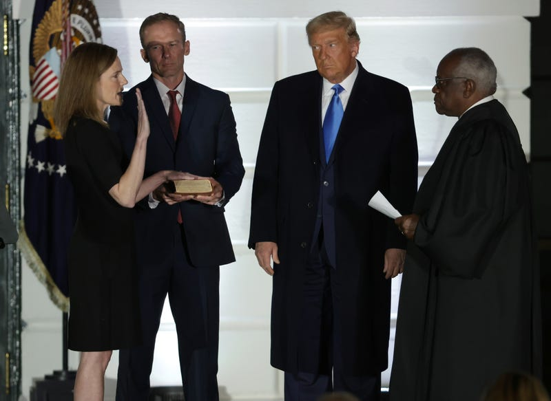 U.S. President Donald Trump (2R) watches as U.S. Supreme Court Associate Justice Amy Coney Barrett (L) is sworn in by Supreme Court Associate Justice Clarence Thomas (R) as her husband Jesse Barrett (2L) holds a bible during a ceremonial swearing-in event on the South Lawn of the White House October 26, 2020 in Washington, DC. The Senate confirmed Barrett's nomination to the Supreme Court by a vote of 52-48.