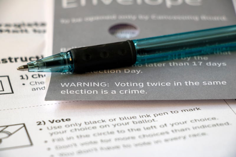 Closeup edge of a mail voting envelope on top of other voter materials, focused on text 'Warning: Voting twice in the same election is a crime' with pen laying on top.
