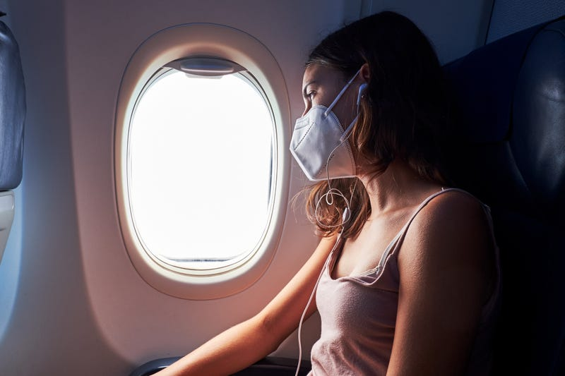 pasajera en un avión con mascarilla
