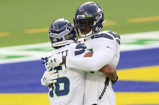 Tyler Lockett and D.K. Metcalf hug in the Rams' end zone.