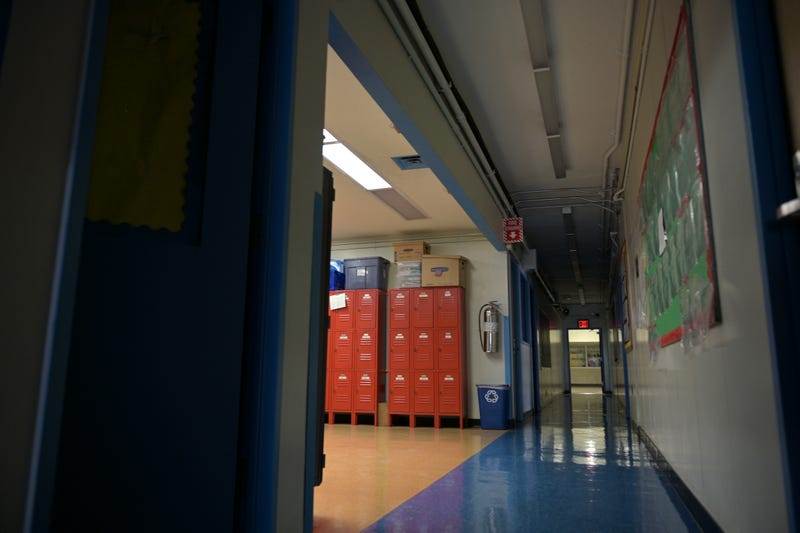A hallway is empty with most of the lights off on what would otherwise be a blended learning school day on November 19, 2020 at Yung Wing School P.S. 124 in New York City