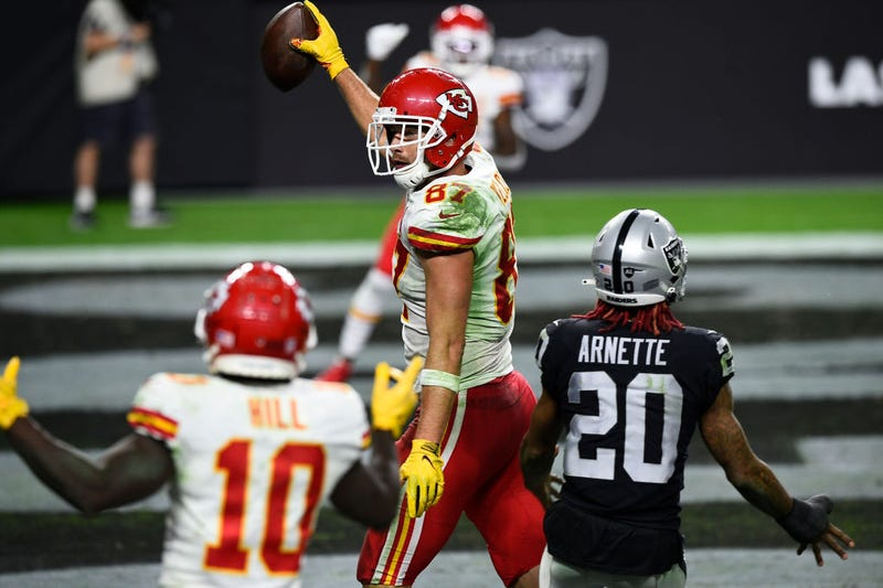 Travis Kelce holds up the football after catching a game-winning touchdown.