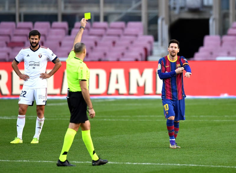 Lionel Messi of Barcelona is shown a yellow card after removing his shirt whilst celebrating after scoring their sides fourth goal while wearing a Newell's Old Boys shirt with the number 10 on the back in memory of former footballer, Diego Maradona, who recently passed away during the La Liga Santander match between FC Barcelona and C.A. Osasuna at Camp Nou on November 29, 2020 in Barcelona, Spain. Sporting stadiums around Spain remain under strict restrictions due to the Coronavirus Pandemic as Government social distancing laws prohibit fans inside venues resulting in games being played behind closed doors.