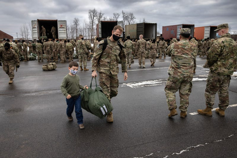 Cal Wasilewski, 5, helps his father U.S. Army Maj. Kurt Wasilewski carry his duffel after soldiers returned home from a 9-month deployment to Afghanistan on December 10, 2020 at Fort Drum, New York, part of the U.S. drawdown from Afghanistan.