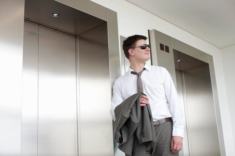 A man in sunglasses with his jacket over his arm waits for an office elevator