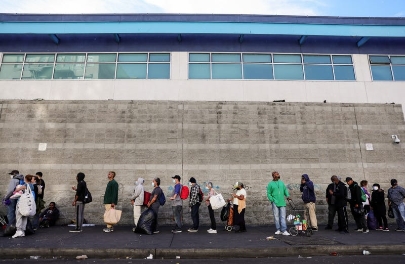 Community members wait in line to receive holiday-themed takeout meals and backpacks with toiletries from the Midnight Mission in Skid Row on Christmas day amid the COVID-19 pandemic on December 25, 2020 in Los Angeles, California.