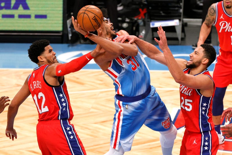 Jarrett Allen #31 of the Brooklyn Nets controls the ball as Tobias Harris #12 and Ben Simmons #25 of the Philadelphia 76ers defend.