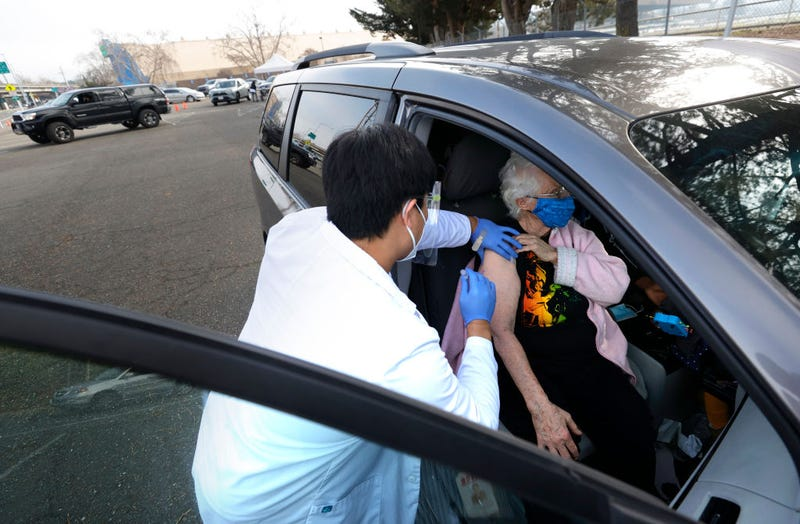 Safeway pharmacist Preston Young (L) administers a Moderna COVID-19 vaccination to Cecile Lusby (R) during a drive-thru COVID-19 vaccination clinic at the Sonoma County Fairgrounds on January 13, 2021 in Santa Rosa, California. Sonoma County health workers received COVID-19 vaccinations during a drive-thru clinic that was hosted by Sonoma County and Safeway.