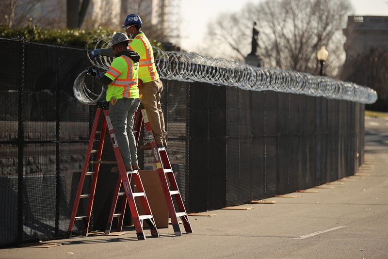 Workers put concertina razor wire along the top of the 8-foot 'non-scalable' fence that surrounds the U.S. Capitol the day after the House of Representatives voted to impeach President Donald Trump for the second time January 14, 2021 in Washington, DC. Thousands of National Guard troops have been activated to protect the nation's capital against threats surrounding President-elect Joe Biden's inauguration and to prevent a repeat of last week's deadly insurrection at the U.S. Capitol.