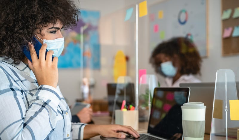 Young people in co-working creative space wearing surgical mask protection and keeping social distance