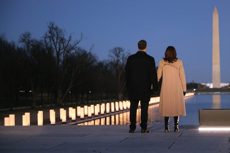 Douglas Emhoff (L) and U.S. Vice President-elect Kamala Harris look down the National Mall as lamps are lit to honor the nearly 400,000 American victims of the coronavirus pandemic at the Lincoln Memorial Reflecting Pool January 19, 2021 in Washington, DC.
