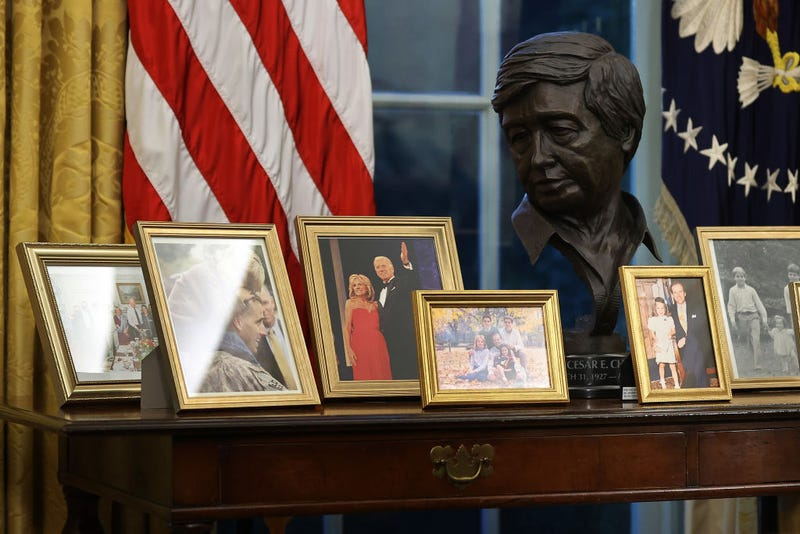 A sculpted bust of Cesar Chavez is seen with a collection of framed photos on a table as U.S. President Joe Biden prepares to sign a series of executive orders at the Resolute Desk in the Oval Office just hours after his inauguration on January 20, 2021 in Washington, DC. Biden became the 46th president of the United States earlier today during the ceremony at the U.S. Capitol.
