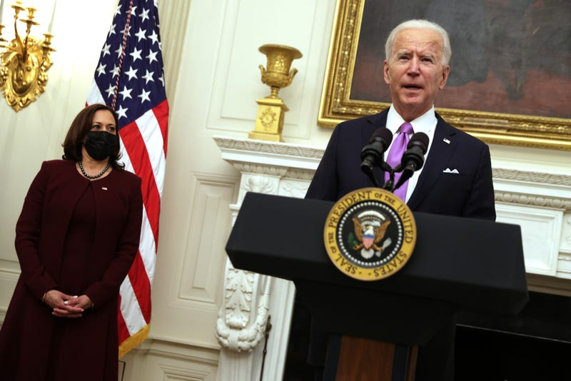 U.S. President Joe Biden speaks as Vice President Kamala Harris looks on during an event at the State Dining Room of the White House January 21, 2021 in Washington, DC. President Biden delivered remarks on his administration's COVID-19 response, and signed executive orders and other presidential actions.