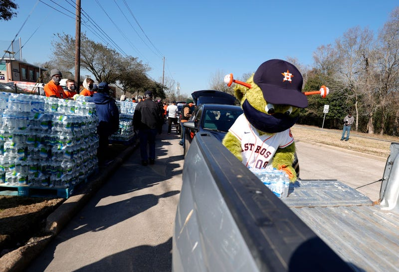Orbit, the Houston Astros mascot, loads a case of water into a truck during a water distribution at the Astros Youth Academy on February 20, 2021 in Houston, Texas. Much of Texas is still struggling with historic cold weather, power outages and a shortage of potable water after winter storm Uri swept across 26 states with a mix of freezing temperatures and precipitation.