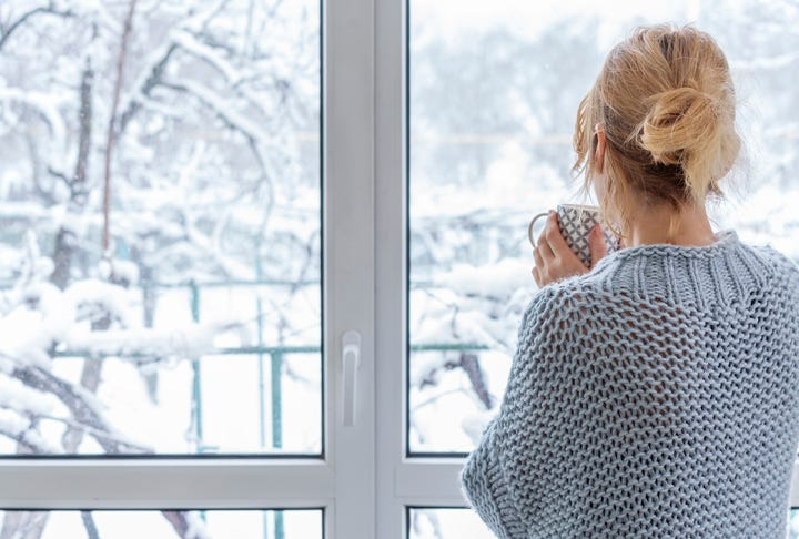 Woman looking out window on to snow covered patio