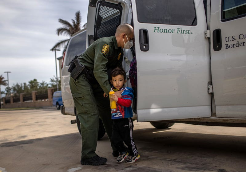 A U.S. Border Patrol agent delivers a young asylum seeker and his family to a bus station on February 26, 2021 in Brownsville, Texas. U.S. immigration authorities are now releasing many asylum seeking families after detaining them while crossing the U.S.-Mexico border. The immigrant families are then free to travel to destinations throughout the U.S. while awaiting asylum hearings.