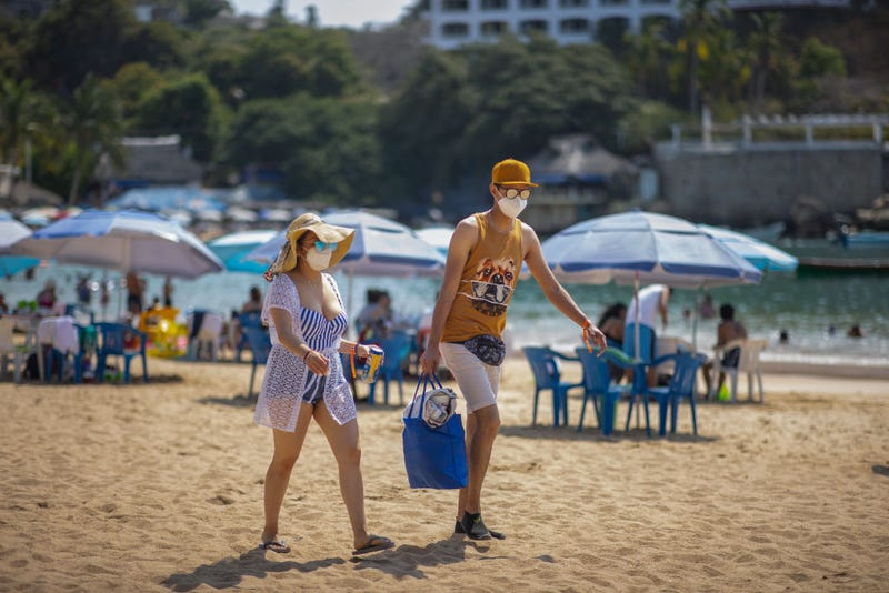 Tourists wearing a mask walk along Caleta beach on March 19, 2021 in Acapulco, Mexico. Acapulco began its vaccination plan for senior citizens on March 17, people over 60 years old will receive the first dose of the vaccine against Covid-19. Acapulco remains as one of the favourite tourist destination for Mexicans.