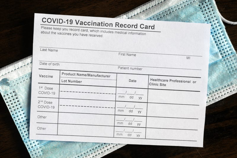 COVID-19 Vaccination Record Card on desk, coronavirus immunization certificate and surgical mask. Top view of paper medical form required for travel. Concept of corona virus vaccine, safety, tourism.