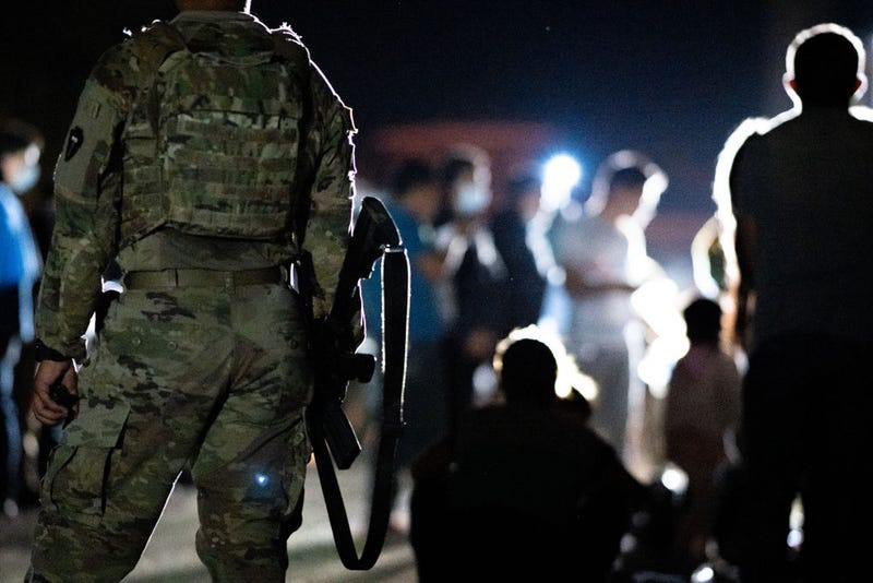 A member of the National Guard stand watch while immigrants wait to be processed after crossing the Rio Grande into the U.S. on June 16, 2021 in Roma, Texas.