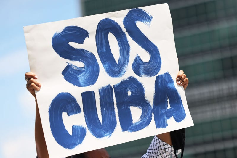 A person holds up a protest sign as people gather calling for help for Cuban protestors