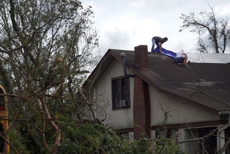 LAPLACE, LOUISIANA - AUGUST 30: Workers tarp the roof of a home damaged by Hurricane Ida on August 30, 2021 in Laplace, Louisiana. Ida made landfall August 29 as a category 4 storm southwest of New Orleans.