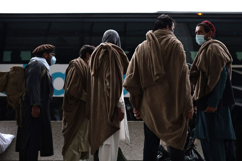 Afghan refugees board a bus at Dulles International Airport.