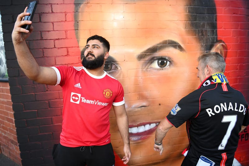 Fans of Manchester United pose for a photograph next to a mural of Cristiano Ronaldo of Manchester United which is located outside the stadium prior to the UEFA Champions League group F match between Manchester United and Villarreal CF at Old Trafford on September 29, 2021 in Manchester, England.