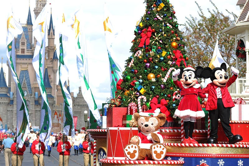 """Mickey and Minnie Mouse wave to the crowd while taping the """"Disney Parks Christmas Day Parade"""" TV special in the Magic Kingdom park at Walt Disney World"""