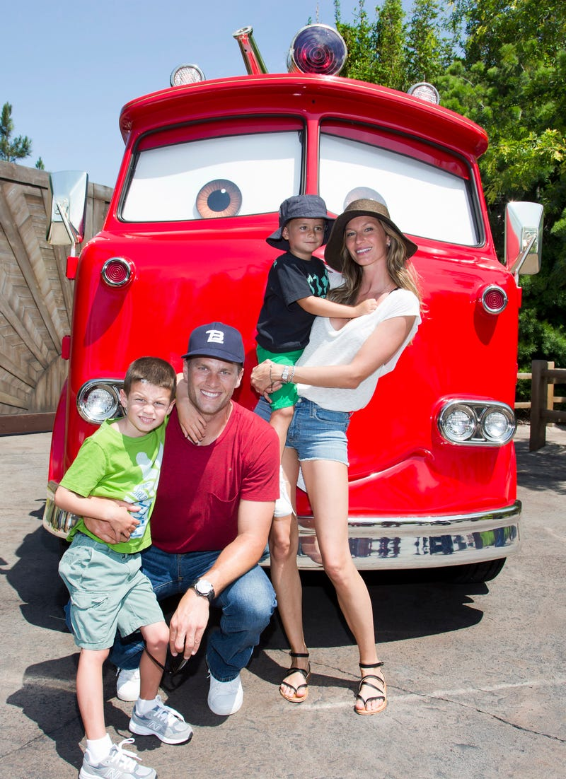 tom brady, gisele bundchen and fam posing with red the fire truck at cars land in disney california
