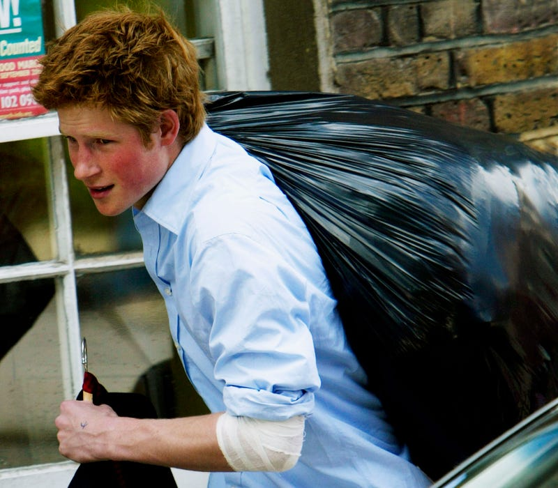 prince harry carrying out a plastic bag of belongings on his last day at eton college in 2003