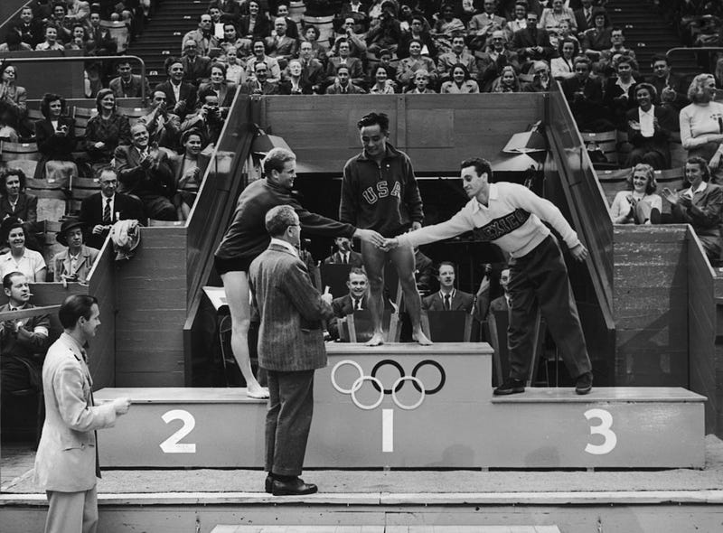 Olympic medal ceremony at the Empire Pool, Wembley. Men's Platform Diving, Bruce Harlan (USA) second congratulates Joaquin Capilla Perez (Mexico) third and Samuel Lee (USA) winner.
