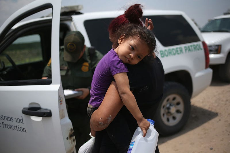 A mother and child, 3, from El Salvador await transport to a processing center for undocumented immigrants after they crossed the Rio Grande into the United States on July 24, 2014 in Mission, Texas.