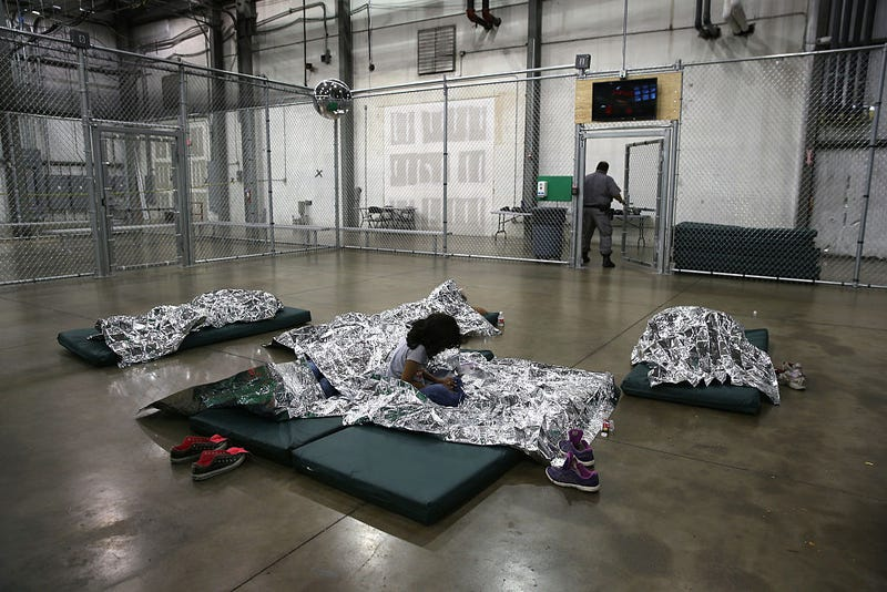 A girl from Central America rests on thermal blankets at a detention facility run by the U.S. Border Patrol on September 8, 2014 in McAllen, Texas