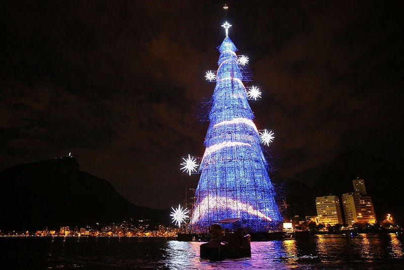 Brazilians paddle past the world's largest floating Christmas tree on December 21, 2014 in Rio de Janeiro, Brazil. The tree is 85-meters tall and features over 3 million light bulbs.