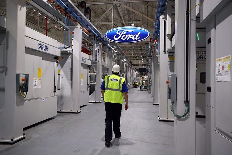 An employee walks past a Ford logo